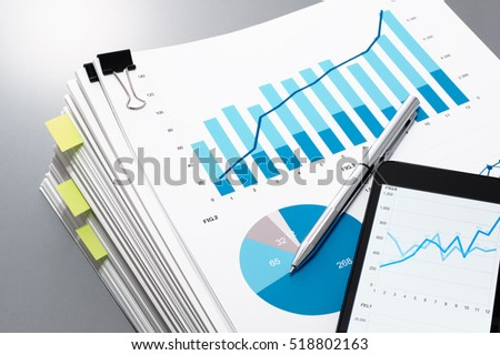 Pile of documents, smart phone and pen on gray reflection background. Many graphs and charts. Concept image of data gathering.