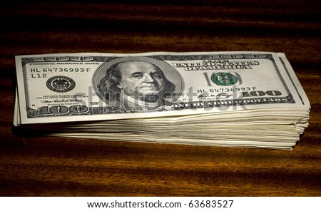 Pile of dollars on wooden table