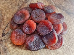 Pile of dried apricot fruit on sun. Organic natural dried apricots from farm on wooden rustic table background. Dark orange dried apricot fruits closeup. Dry fruits healthy sweet food hydrated on sun