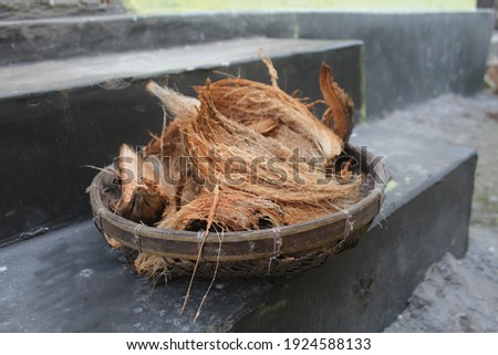 Pile of dried coconut husk peel on plate. The outer layer is a natural fiber extracted from the husk of coconut and used in products such as floor mats, doormats, brushes and mattresses and for prayer Stock photo ©