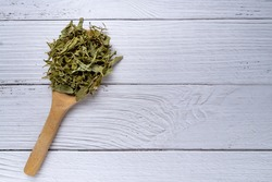 pile of dried stevia rebaudiana bertoni in wooden spoon on white wood background. Natural sweetener from stevia plant.