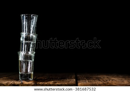 Pile of empty shot glasses (close-up shot) on wooden background #381687532