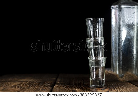 Pile of empty shot glasses (close-up shot) on wooden background #383395327