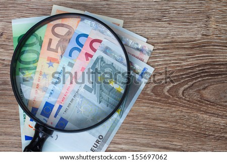 pile of euro banknotes under looking glass