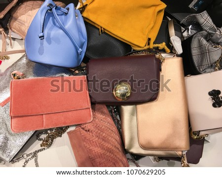 Pile of fashion women handbags in store