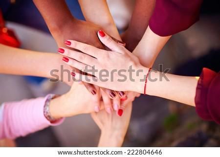pile of female multiracial hands in union sign