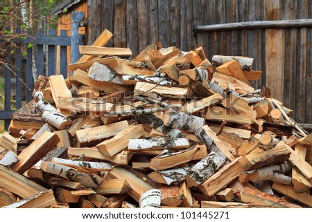 Pile of firewood against old wooden fence
