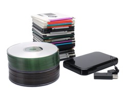 Pile of floppy disks, cd-roms, external hard drive and pen drive over white