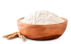 Pile of flour in a wooden plate with spikelets of wheat close-up on a white background. Isolated