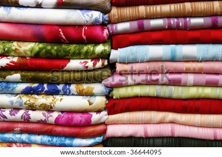 Pile of folded fabrics and shawls (scarfs) at the market