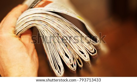 Pile of folded newspapers in hand. Fresh daily papers delivered to the office. Postman is holding lots of pages with business news. Articles, headlines and photos blurred for background #793713433