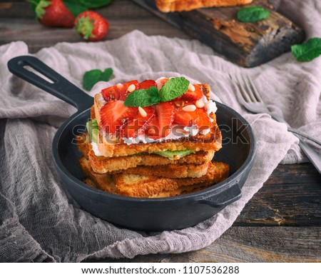 pile of French toast from white bread with cottage cheese, strawberries in a black cast-iron round frying pan with a handle on a gray wooden table