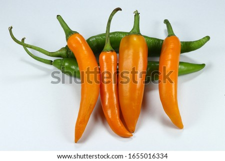 Pile of fresh and organic hot Chili pepper,  Orange and green cayenne chili isolated on white background. Popular hot and spicy ingredient in Asia.