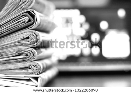 Pile of Fresh Morning Newspapers and Laptop at Office. Latest Financial and Business News in Paper and on Screen Pages with Information (Headlines, Articles, Photo). Stacked Journals and Computer