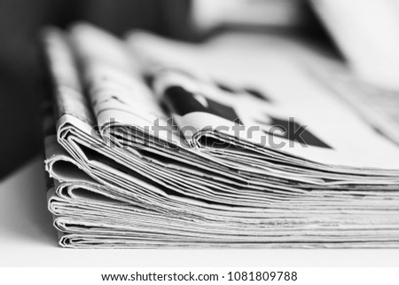 Pile of fresh morning newspapers on the table at office. Latest financial and business news in daily paper. Pages with information (headlines, articles, photos, text). Folded and stacked journals #1081809788