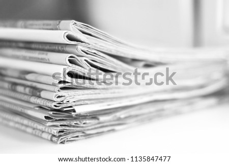 Pile of fresh morning newspapers on the table at office. Latest financial and business news in daily paper. Pages with information (headlines, articles, photos, text). Folded and stacked journals      #1135847477