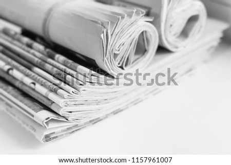 Pile of fresh morning newspapers on the table at office. Latest financial and business news in daily paper. Pages with information (headlines, articles, photos, text). Folded and rolled journals      #1157961007