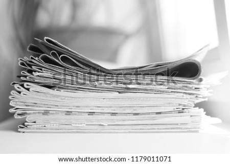Pile of fresh morning newspapers on the table at office. Latest financial and business news in daily paper. Pages with information (headlines, articles, photos, text). Folded and stacked journals      #1179011071