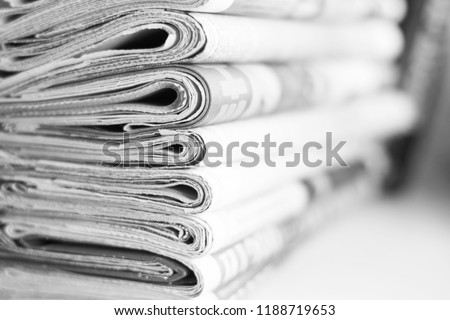 Pile of fresh morning newspapers on the table at office. Latest financial and business news in daily paper. Pages with information (headlines, articles, photos, text). Folded and stacked journals      #1188719653