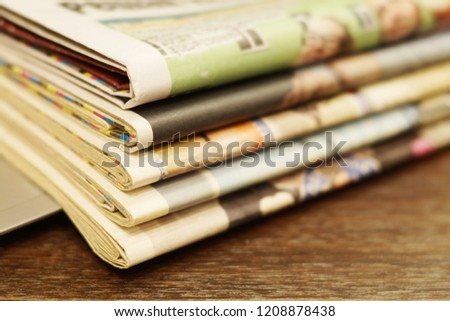 Pile of fresh morning newspapers on the table at office. Latest financial and business news in daily paper. Pages with information (headlines, articles, photos, text). Folded and stacked journals      #1208878438