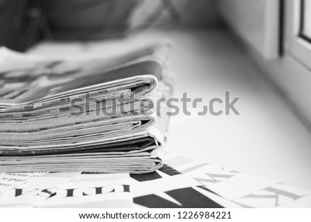 Pile of fresh morning newspapers on the table at office. Latest financial and business news in daily paper. Pages with information (headlines, articles, photos, text). Folded and stacked journals      #1226984221