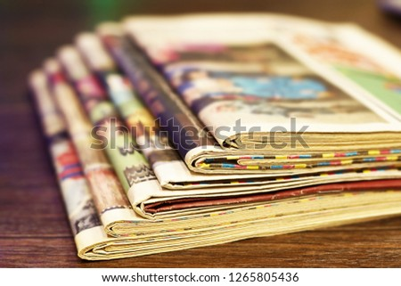 Pile of fresh morning newspapers on the table at office. Latest financial and business news in daily paper. Pages with information (headlines, articles, photos, text). Folded and stacked journals      #1265805436