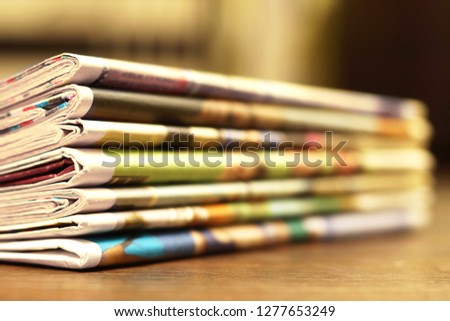 Pile of fresh morning newspapers on the table at office. Latest financial and business news in daily paper. Pages with information (headlines, articles, photos, text). Folded and stacked journals      #1277653249