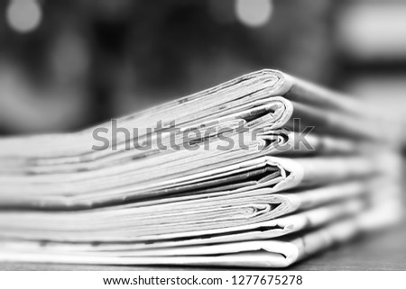 Pile of fresh morning newspapers on the table at office. Latest financial and business news in daily paper. Pages with information (headlines, articles, photos, text). Folded and stacked journals      #1277675278