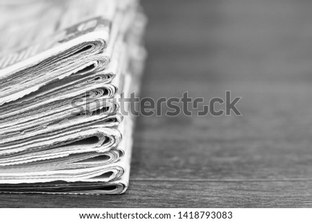 Pile of fresh morning newspapers on the table at office. Latest financial and business news in daily paper. Pages with information (headlines, articles, photos, text). Folded and stacked journals