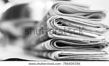 Pile of fresh morning newspapers on the table at office. Latest financial and business news in daily paper. Pages with information (headlines, articles, photos, text). Folded and stacked journals #786606586