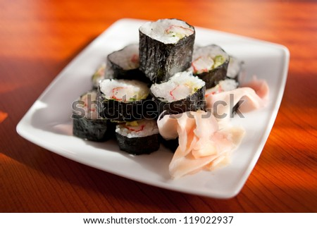 Pile of fresh sushi with ginger Japanese food rolls sliced lying on white plate and soya sauce in glass bowl on table, horizontal orientation, nobody. - stock photo