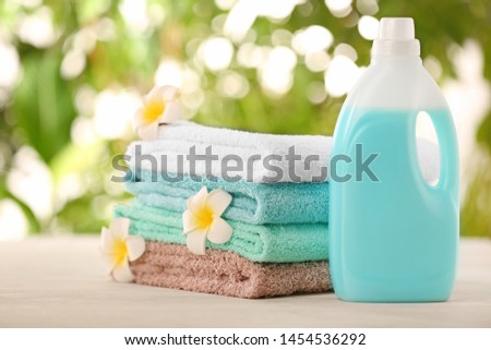 Pile of fresh towels, flowers and detergent on table against blurred background Foto stock ©