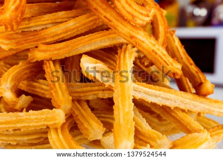 Pile of freshly made deep fried churros sweet pastry traditional for Spain Portugal Latin America at street cafe. Scrumptious treat appetizing golden crust. Authentic city life atmosphere street food