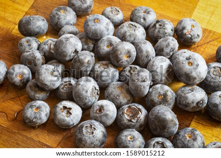 Pile of freshly washed blueberries on a wooden board. Fresh, healthy food_
