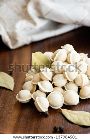 Pile of frozen mini pelmeni on a wooden board, selective focus