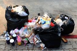 Pile of Garbage plastic black and trash bag waste many on the footpath, pollution trash, Plastic Waste and Bag Foam tray Garbage many on floor, Waste plastic