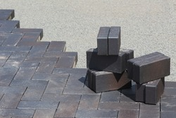 pile of gray brick stones on the pavement road and gravel. laying bricks on the street. background for construction, copy space