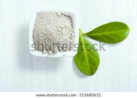 pile of gray cosmetic clay at old white wooden table