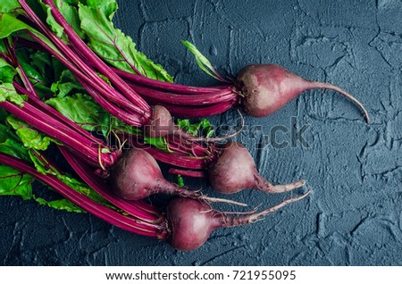 Pile of homegrown organic young beets with green leaves on dark stone table. Fresh harvested beetroots on black concrete background. Top view.