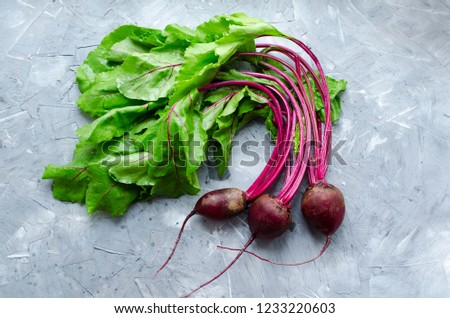 Pile of homegrown organic young beets with green leaves on the table. Fresh harvested beetroots on grey concrete background. Top view.