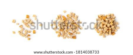 Pile of homemade bread croutons isolated on white background top view. Crispy bread cubes, dry rye crumbs, rusks, crouoton or white roasted crackers cube heap collection