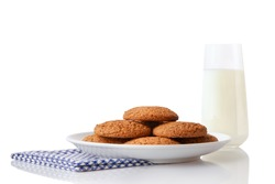 Pile of homemade oatmeal cookies on white ceramic plate on blue napkin and glass of milk, isolated on white background