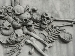 Pile of human skulls on stone surface. Wall of Skulls. A stone wall with skull carvings.