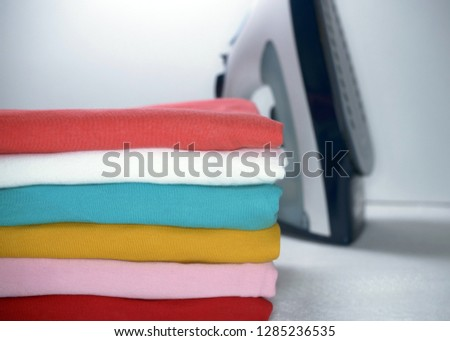pile of ironed clothes and iron on white background #1285236535
