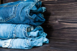 Pile of  jeans clothes on wooden  background.