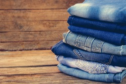 Pile of  jeans clothes on wooden background. Toned image.