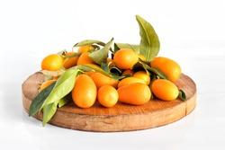 Pile of kumquat fruit, chinese tangerine, on wooden cutting board isolated on white.