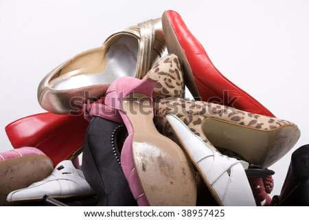 Pile of ladies shoes against white background.