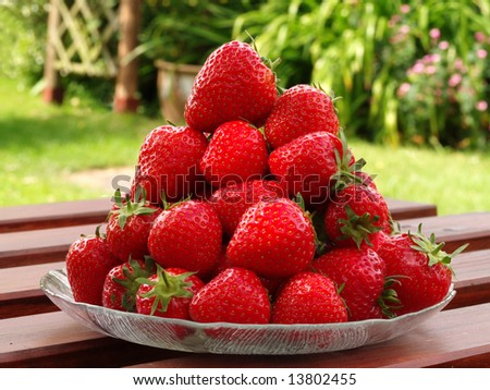 Pile of large, ripe, delicious strawberries on a glass plate on a picnic table in a sunny garden