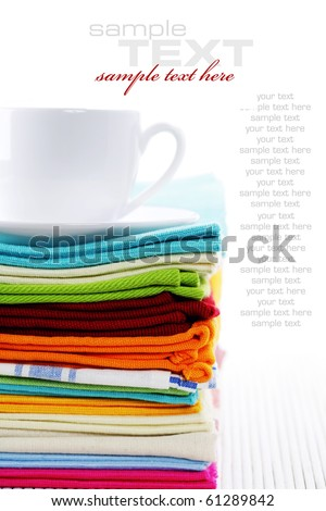 Pile of linen kitchen towels and cup of tea or coffee over white (with sample text) - stock photo